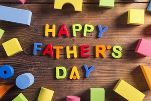 Happy fathers day sign and colorful toys laid on wooden background.