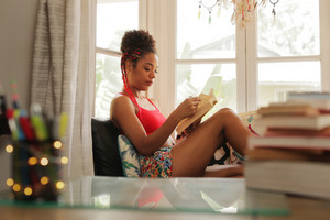 Happy female student reading book and sitting on sofa. Young african american woman relaxing, black girl lying on couch. Hispanic people and lifestyle, leisure and relaxation at home