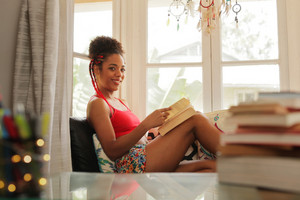 Happy female student reading book and sitting on sofa. Young african american woman relaxing, black girl smiling at camera. Hispanic people and lifestyle, leisure and relaxation at home
