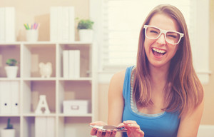 Happy fit young woman laughing while using her cellphone at home