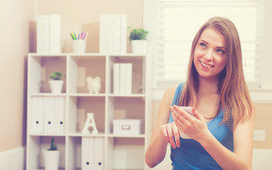 Happy fit young woman using her cellphone at home