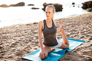 Happy fitness woman doing stretching exercises on the beach