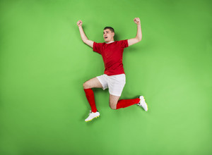Happy football player celebrating victory. Studio shot on a green backroung.