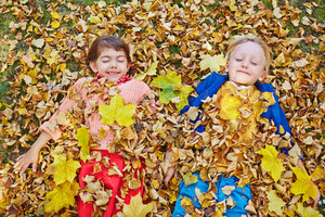Happy friends with closed eyes lying in dry autumn leaves