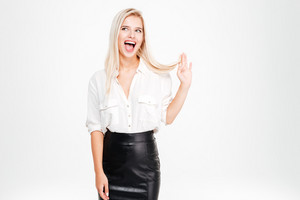 Happy funny young businesswoman standing and having fun over white background