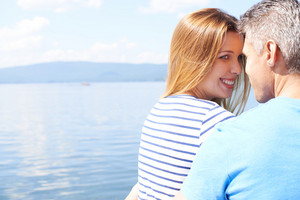 Happy girl and young man having romantic vacation by the sea