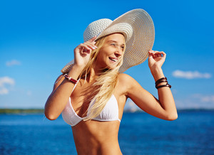 Happy girl in bikini and hat spending time at summer resort