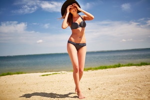 Happy girl in bikini and hat walking down sandy beach