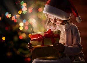 Happy girl in Santa cap looking at wonderful Christmas present in giftbox