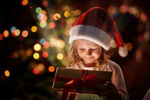 Happy girl in Santa cap opening box with magic gift