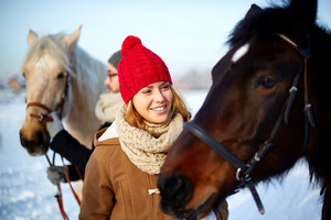 Happy girl in winterwear looking at horse outdoors