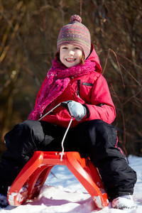 Happy girl in winterwear sitting on sledge in park