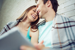 Happy girl laughing while cuddling to guy
