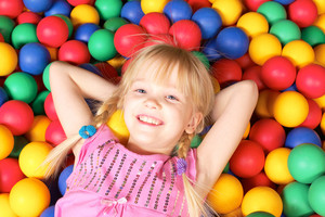 Happy girl lying on colorful balls and smiling