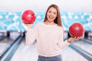 Happy girl with bowling balls looking at camera