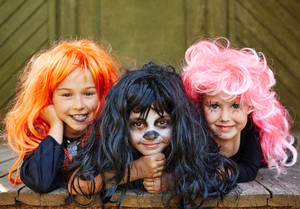 Happy girls in bright wigs looking at camera on Halloween day