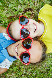 Happy girls in sunglasses looking at camera with smiles while relaxing outdoors