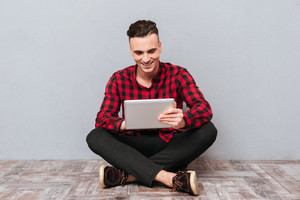 Happy handsome Man in shirt sitting on the floor with tablet. Isolated gray background