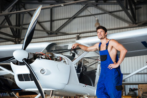 Happy handsome mechanic in overall resting in front of the plane in a shed