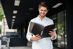 Happy handsome young businessman standing and looking through documents in folder