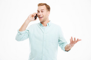 Happy handsome young businessman talking on mobile phone over white background
