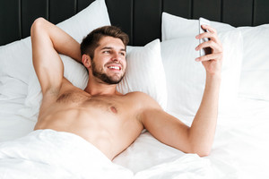 Happy handsome young man lying and using smartphone in bed