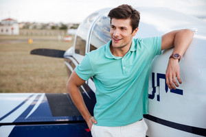 Happy handsome young man standing in field near small private airplane