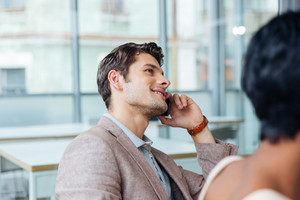 Happy handsome young man talking on cell phone in office