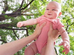 Happy infant baby girl being held up in the air by her parent