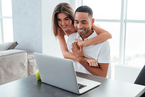 Happy interracial couple with laptop. so cool portrait. in kitchen