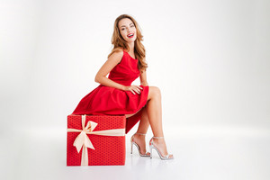 Happy joyful woman in red dress having fun while sitting on the big gift box isolated on a white background