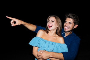 Happy joyful young couple laughing and pointing away at night