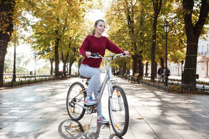 Happy lady dressed in sweater walking with her bicycle outdoors. Look aside.
