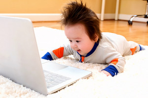 Happy little baby boy with a laptop computer
