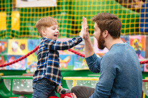 Happy little boy and father taking high five and playing at indoor amusement park