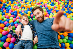 Happy little boy and his father lying and playing at pool with colorful balls