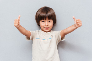 Happy little boy standing and showing thumbs up over gray background