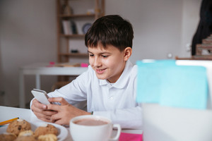 Happy little boy using cell phone and having breakfast at the table
