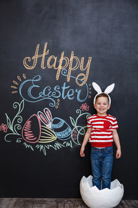 Happy little boy wearing rabbit ears and standing inside big cracked eggshell over chalk board with easter doodles background