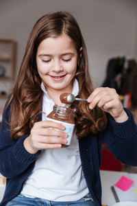 Happy little girl eating chocolate spread from jar by spoon