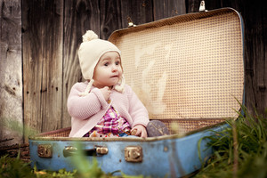 Happy little girl in warm clothes is sitting in retro suitcase in front of the fence in autumn nature