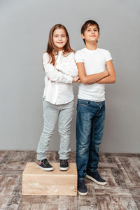 Happy little girl standing with arms crossed on box near tall smiling boy