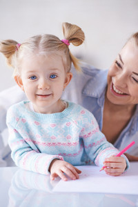 Happy little girl with crayon and her mother near by