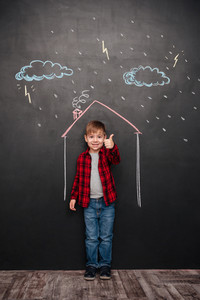 Happy little kid standing in house on the chalkboard with drawings of a rain. Looking at camera while making thumbs up gesture. Looking at camera.