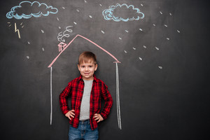 Happy little kid standing in house on the chalkboard with drawings of a rain. Looking at camera.