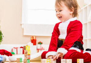 Happy little toddler girl playing with her Christmas toys with a santa costume