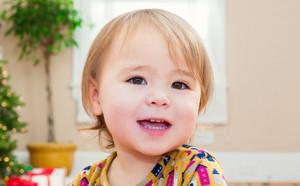 Happy little toddler girl smiling inside her house