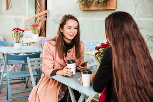 Happy lovely young woman drinking coffee and talking to her friend in outdoor cafe