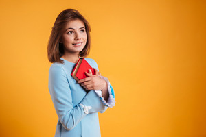 Happy lovely young woman holding red book over yellow background