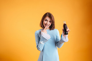 Happy lovely young woman standing and holding bottle of soda over yellow background